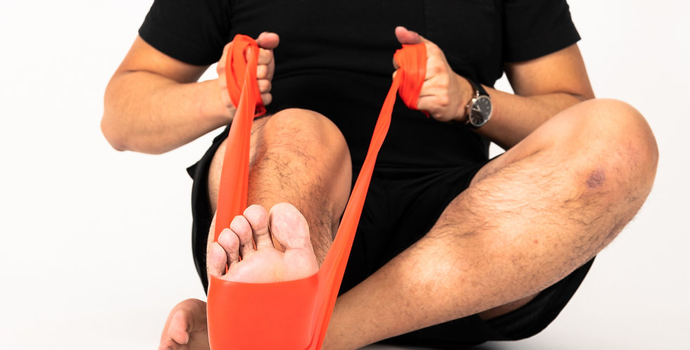 A man sitting on the floor holding Sup-R resistance theraband around the arch of his foot pulling it for back strengthening
