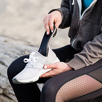 A woman sitting on a bench sliding her custom foot orthotics for plantar fasciitis into a pair of white athletic shoes.