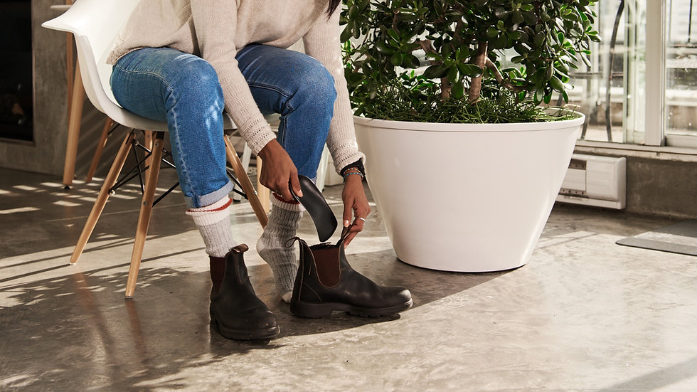 Close up a woman bending down to put her custom foot orthotics into a pair of Blundstone boots