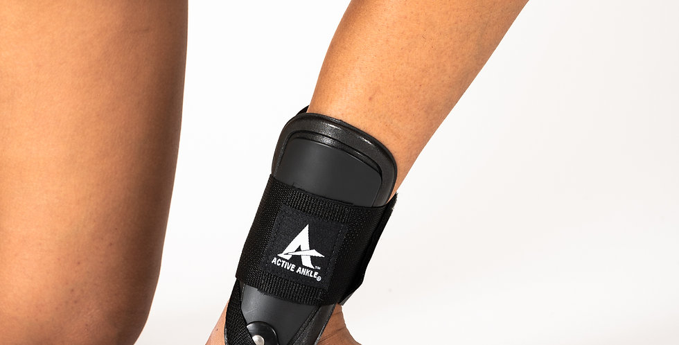 A woman kneeling on the floor wearing a black Active Ankle T2 ankle brace with hinged plastic stays for ankle sprains