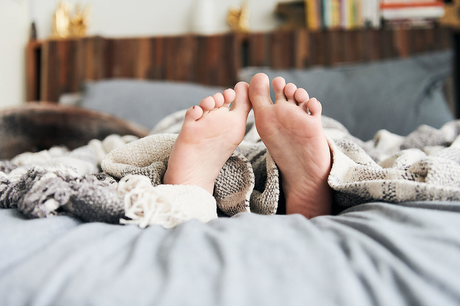 A close up of the bottom of a pair of feet with flat arches sticking out from under a beige blanket