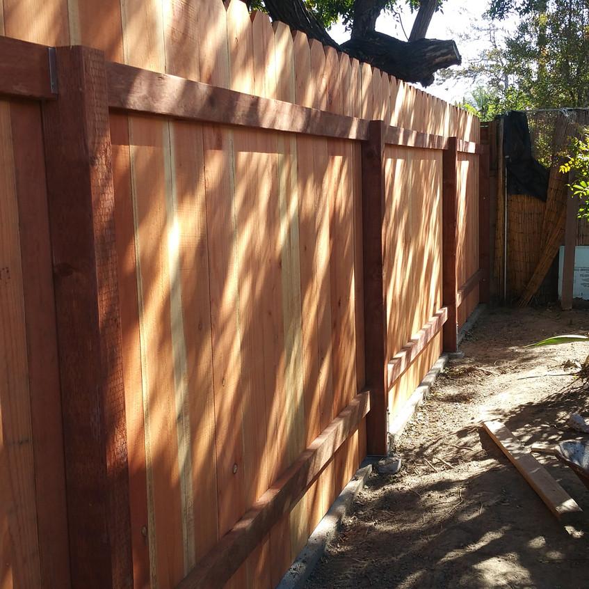 Treated post, redwood fence.
