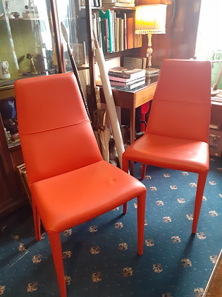 A PAIR OF MODERNIST ORANGE LEATHERETTE UPHOLSTERED HIGH BACKED CHAIRS