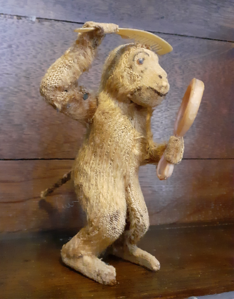 A vintage automated plush covered monkey.