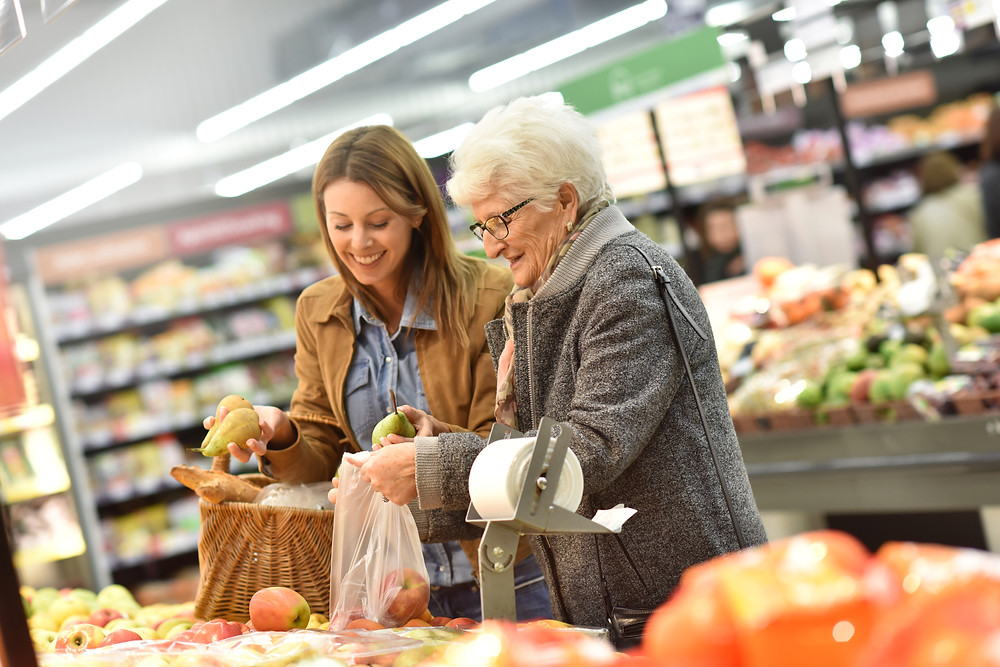 Young woman in grocery store helping elderly woman
