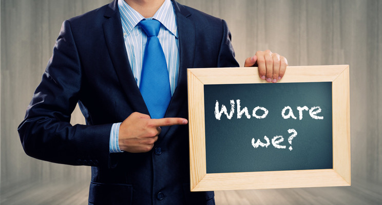 Business man holding chalk board in one hand and pointing to it with the other. On the chalk board reads 'Who are we?'