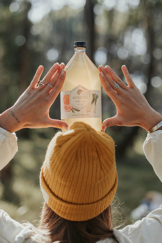Una chica con gorro de lana naranja sosteniendo en su cabeza una botella de Bendita Kombucha de Pomelo y lemongrass. Se filtra la luz por la botella.