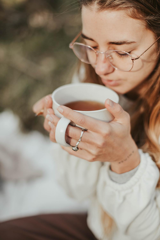 Mujer joven con lentes sosteniendo una taza de té con sus manos sintiendo el aroma