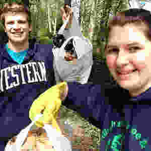 Jenica and her boyfriend holding bags of waste picked up during a litter clean-up.