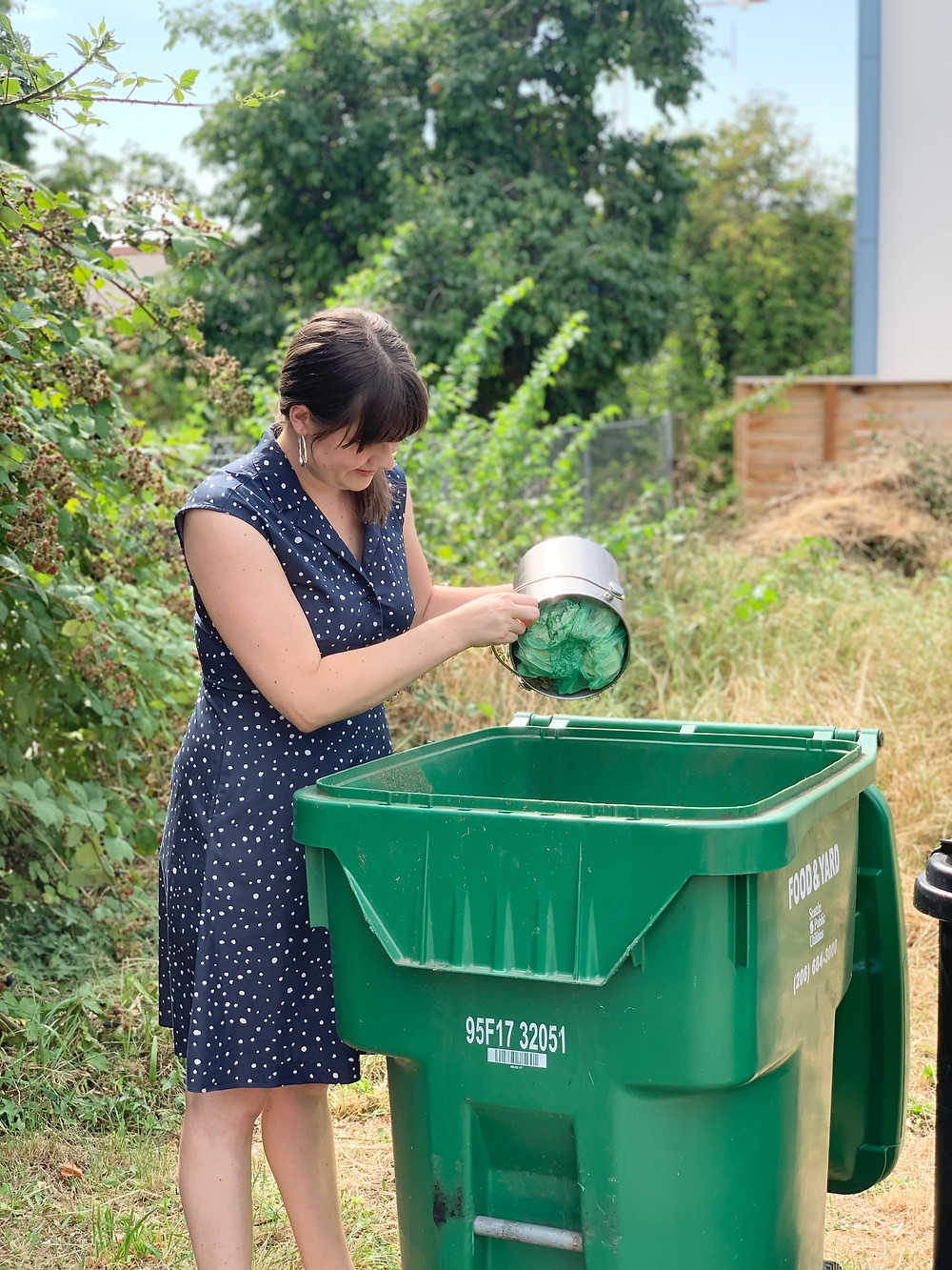 Jenica dumping her compost pale into a curbside green waste bin