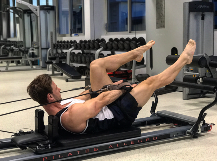 "Studio Athletica personal trainer Christopher Klarich demonstrating the ""criss-cross"" movement on the Pilates reformer"