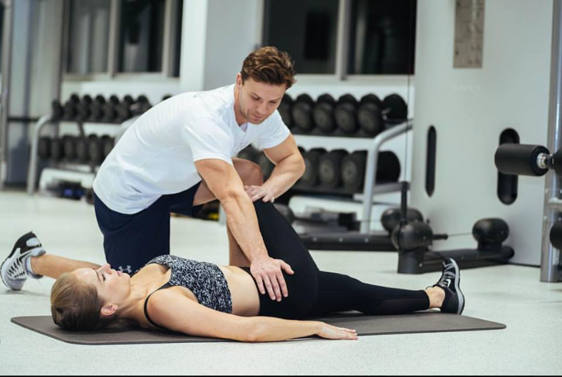 Personal trainer Chris stretching out a client after a session.