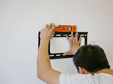 Asian technician hands holding a TV wall