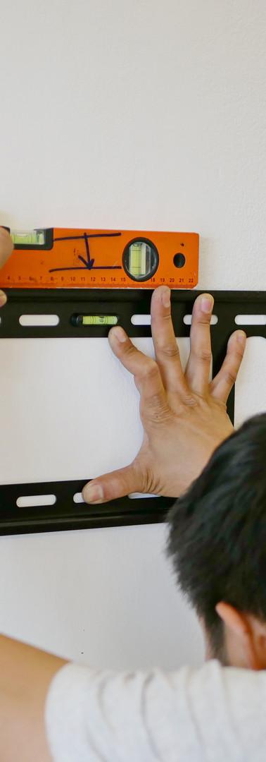 Asian technician hands holding a TV wall
