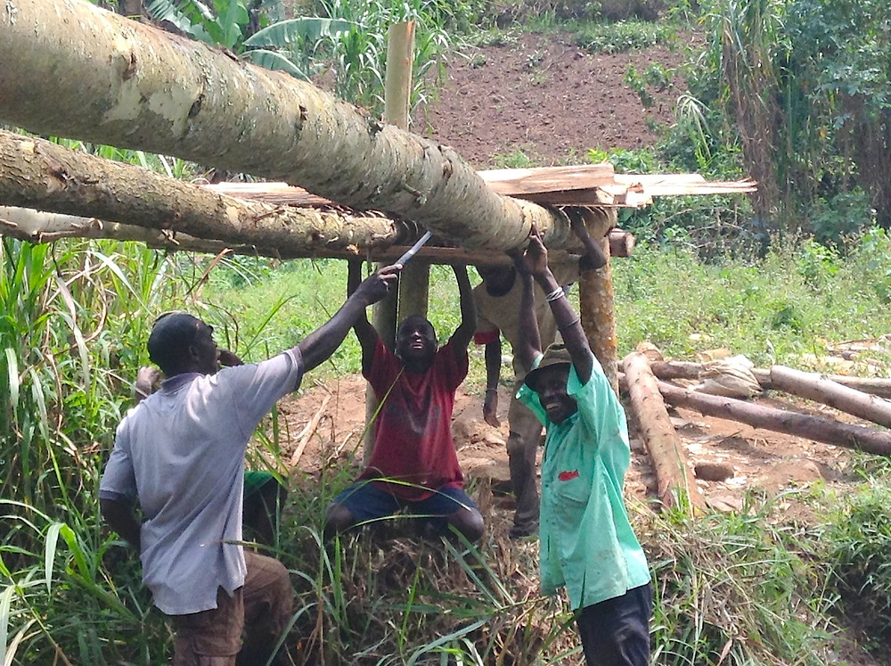 Carpenter Jackson helps direct the Batwa men how to build