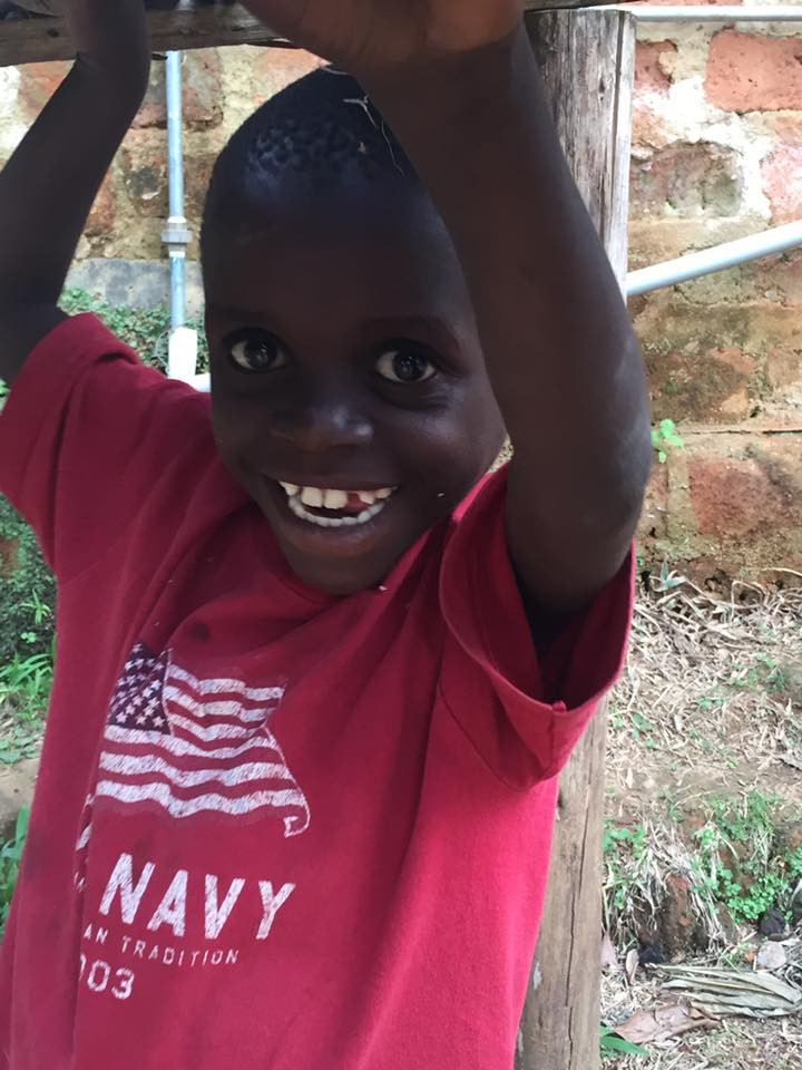 A Batwa child named Beckham in 2016 with a big smile and wearing a USA t-shirt