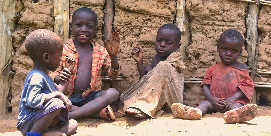 Four Batwa pygmy children sit in the dirt by their mud home wearing dirty clothing and one waves