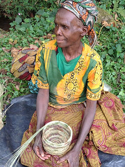 Frida a Batwa elder female holds a basket she is in the process of weaving