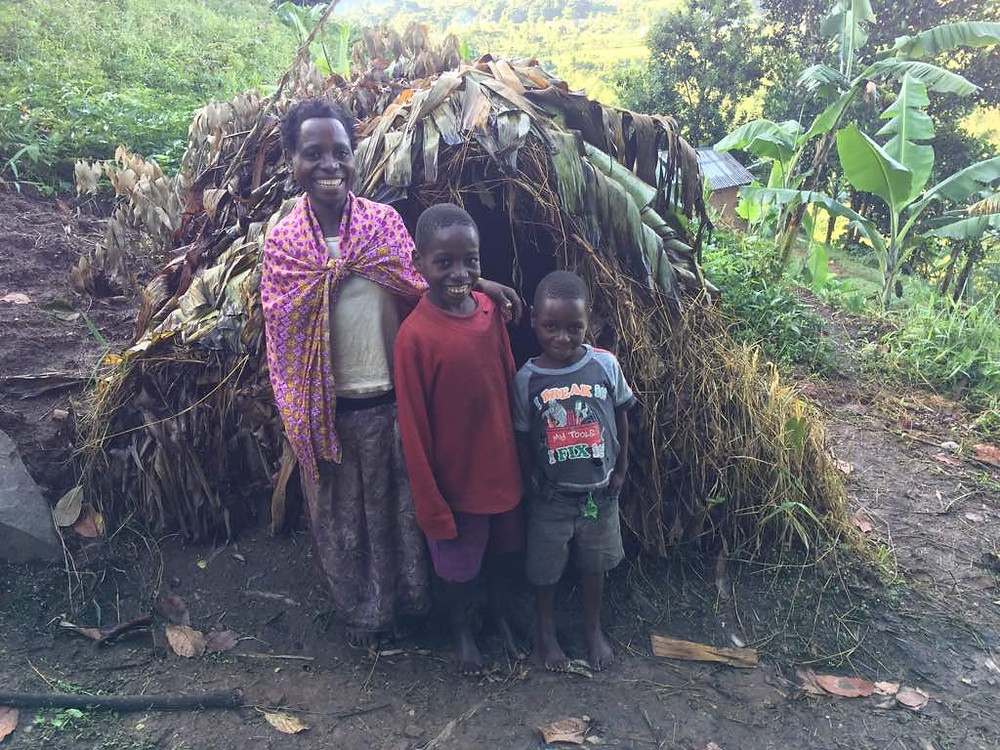 Batwa mother standing by her two children near a traditional hut made from leaves and sticks