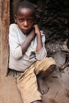 A Batwa child sits in the dirt and ash with a sickly look and dirty clothing