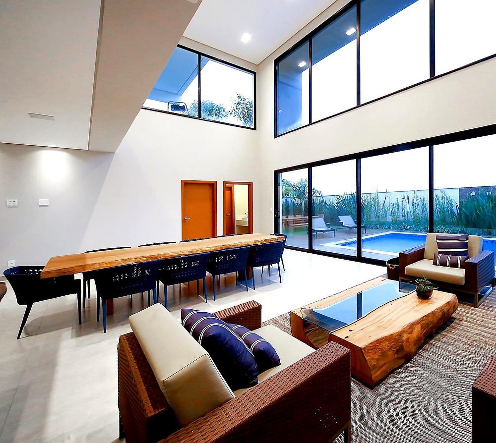 Decoração com mesa de jantar com pés em madeira e mesa de centro de tronco com vidro. Design moderno que deixa seu ambiente ainda mais aconchegante.