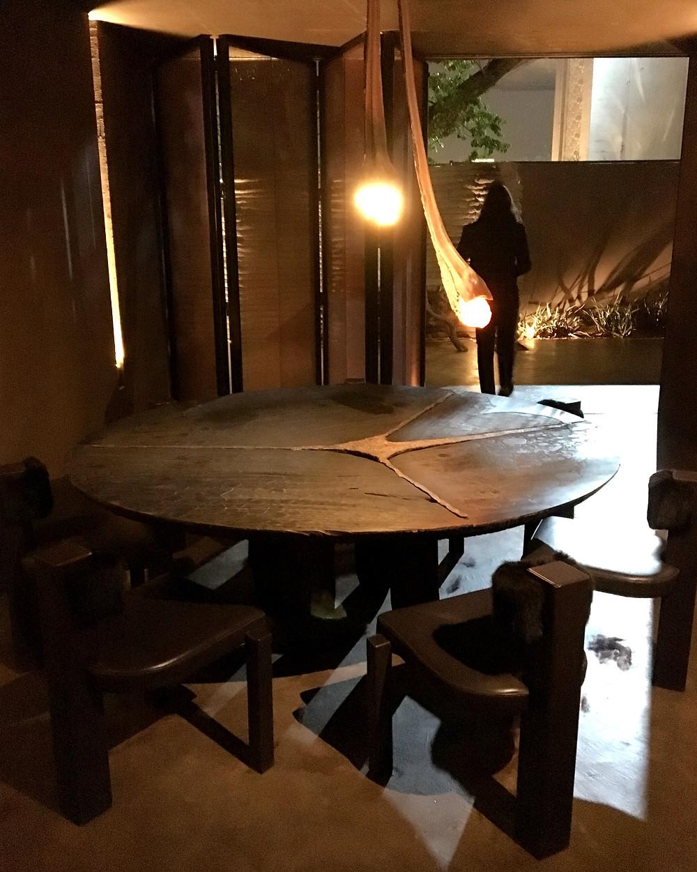 Mesa de Jantar de Madeira redonda com fundição de metal e linhas orgânicas.