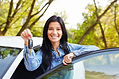 Happy Woman Driver Showing Car Keys And Leaning On Car Door.jpg