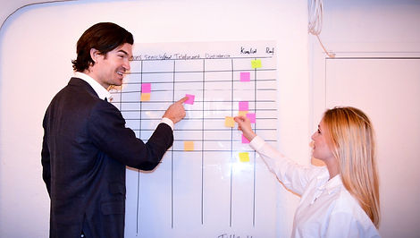 Två personer står vid en whiteboard-tavla