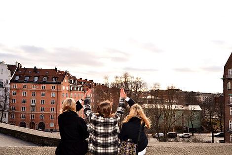 Tre personer sitter på en mur och gör high five