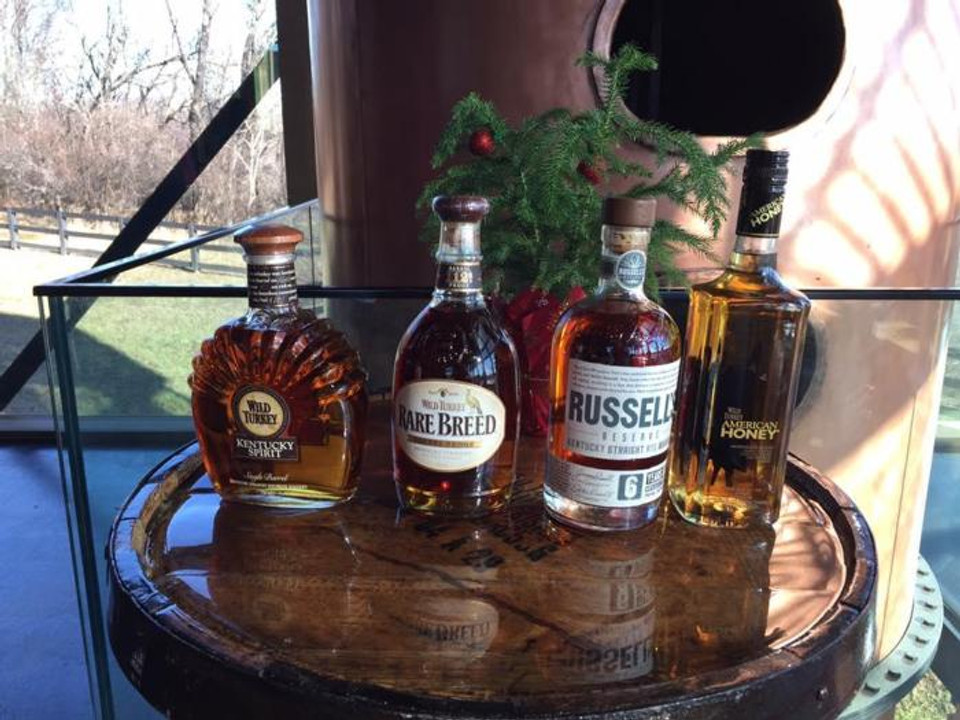Bottles of Wild Turkey Kentucky Spirit, Wild Turkey Rare Breed, Russell's Reserve, and American Honey on a bourbon barrel.
