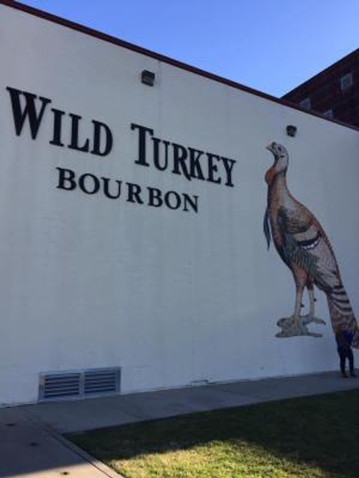 Exterior of Wild Turkey distillery with sign and large painting of a turkey.