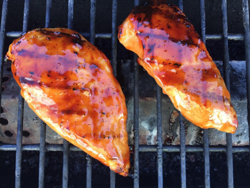 Two porkchops covered with the maple apple bourbon glaze cooking on a grill.