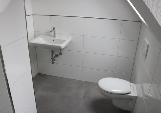 Die Gestaltung des Bades erfolgte mit weißem Fliesenbelag sowie weißem Sanitäreinrichtungen