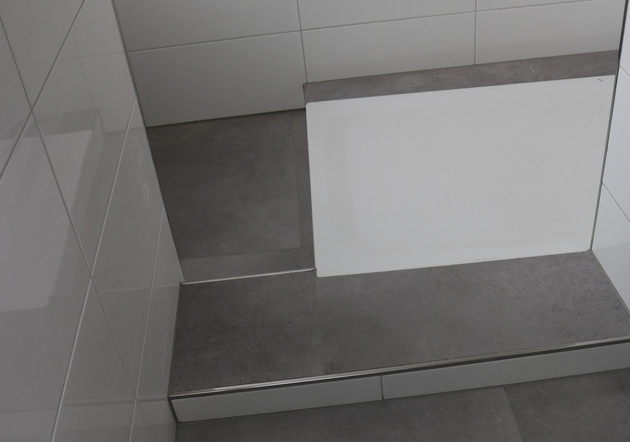 Das Badezimmer ist mit einer Dusche ausgestattet; die Warmwasserversorgung erfolgt über die Fernwärmeanlage