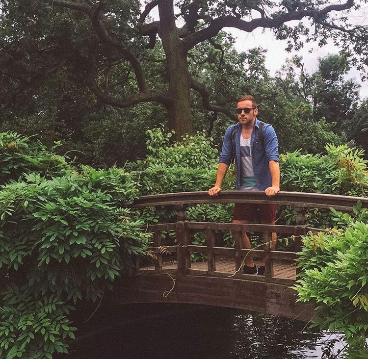 Steven of the Anxious Adventurer poses for a picture on a bridge in the woods on an international travel trip