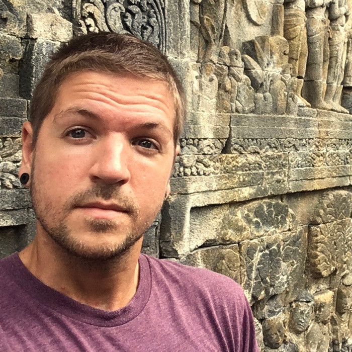 Timm, author, creator and travel blogger of Llama Socks Travel Guide posing for a selfie at some ancient ruins in Cambodia. He is a solo gay male traveler.