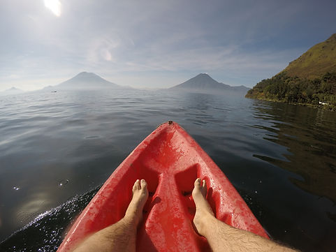 a mans feet while kayaking on Lake Atitlan with volcan fuego in the distance
