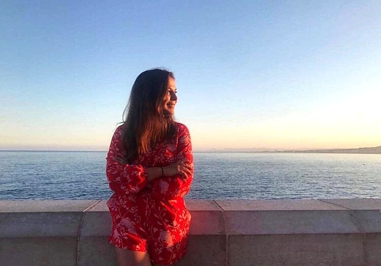 a female traveler in a red dress on the coast posing for a photo