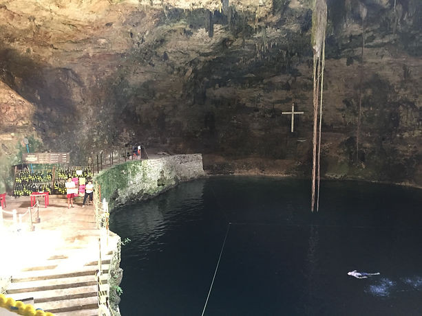 a cenote in Mexico's Yucatan Peninsula with a cross in the background