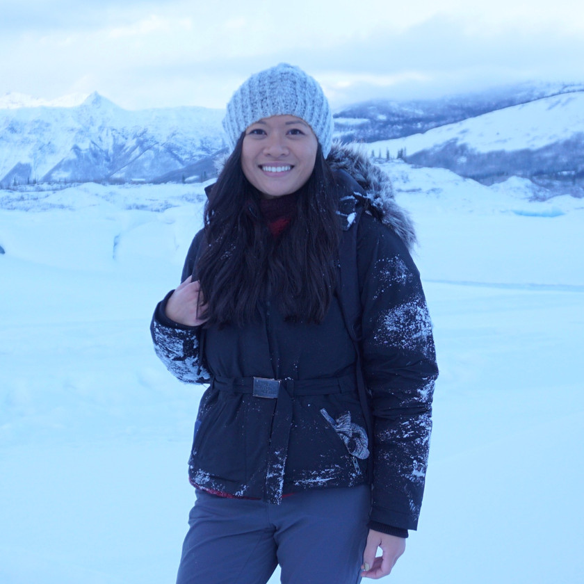 female solo traveler poses for a picture in a blizzard in iceland