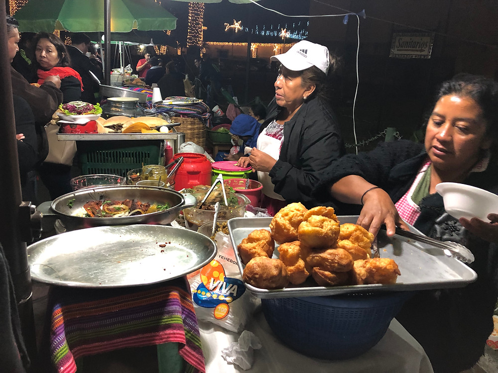 an evening market stand in Antigua, Guatemala where women are selling sweetened fried dough on the street