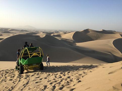 Sanboarding ATV trip through the sand dunes in Huacachina Peru