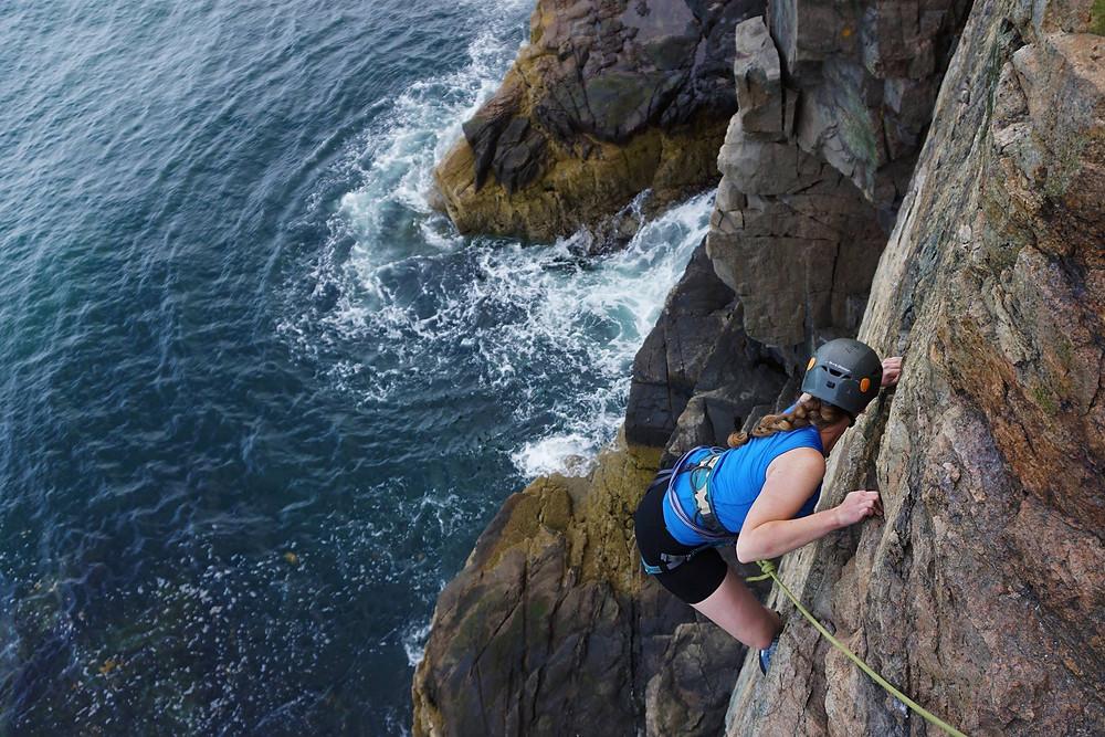 a female solo traveler takes a photo while climbing a cliff over the ocean