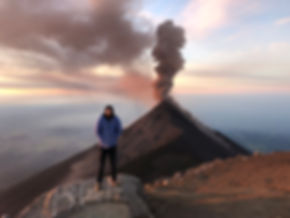 a man posing next to volcan fuego on the acatenango volcano hike near Antigua Guatemala during sunrise