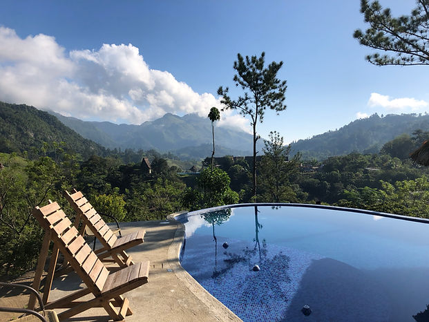 a pool and sun bathing chairs overlooking the jungles in Semuc Champey, Guatemala at Vista Verde Hostel