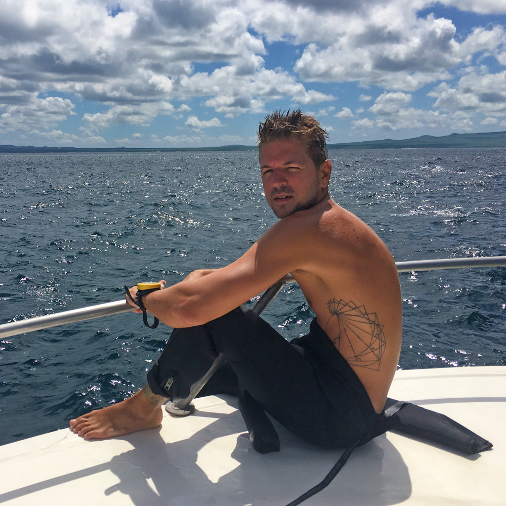 Timm, author, creator and travel blogger of Llama Socks Travel in a wetsuit on a boat before scuba diving underwater. He is a solo gay male traveler