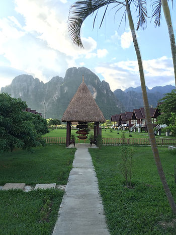 a view of the limestone cliffs and thatched roof homes in Vang Vieng, Laos