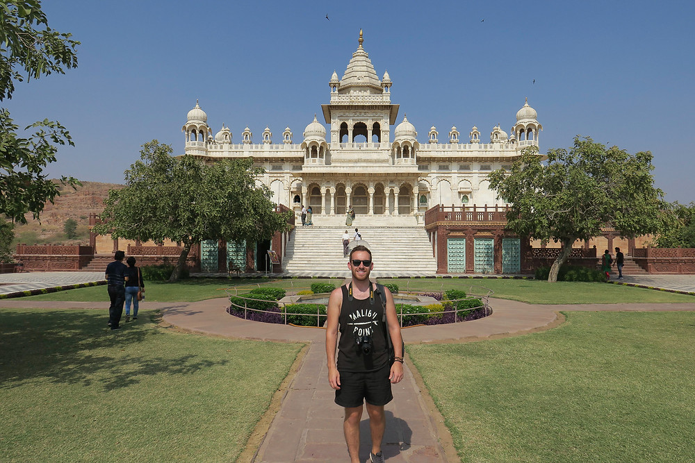 Steven of The Anxious Adventurer poses for a picture in front of a beautiful white palace while traveling and backpacking internationally