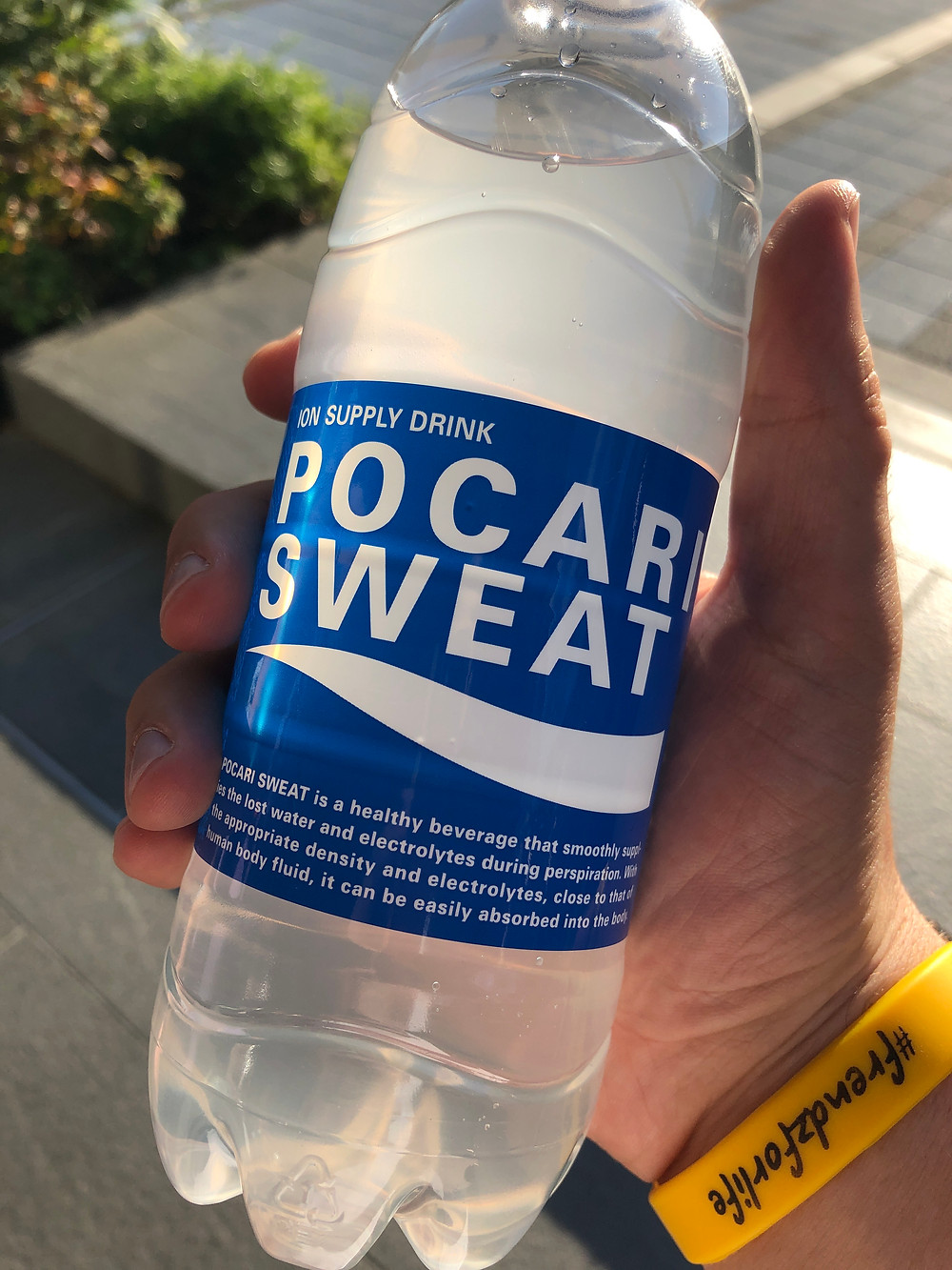 a traveler holding a bottle of Pocari Sweat, an electrolyte drink, in Tokyo Japan