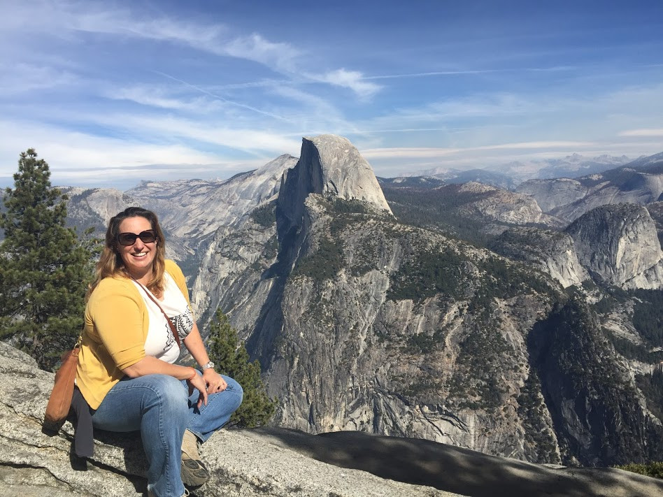 Meredith from Beautiful Voyager posing for a picture in Yosemite National Park in California overlooking mountains and forests